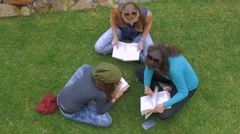 Overhead of three teenage girls reading books on the green grass in slowmo - stock footage