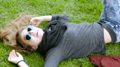 A young teenage girl is tickled and laughing while lying on the grass in slowmo Stock Footage