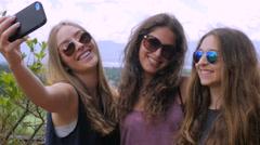 Three best friend teenage girls take a selfies and laugh handheld in slow motion Stock Footage