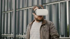 Bearded attractive man uses virtual reality glasses in the urban space. 4k Stock Footage