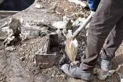 Unknown worker with a shovel clearing construction debris Stock Photos
