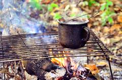 Tourist fire with a mug of boiling water on Camping Stock Photos
