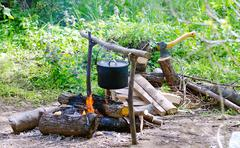 Tourist pot of water hanging over a fire of wood in the Camping Stock Photos