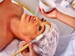 Woman middle-aged take face massage in spa salon. Stock Photos
