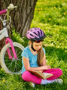 Bikes cycling girl wearing helmet reads book. Stock Photos