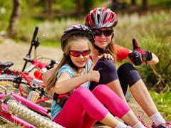 Bikes cycling happy family sitting near bicycles. Stock Photos