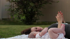 Young Grandmother plays with infant grandson on grass Stock Footage