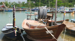 Small fishing boats moored in the bay area in the fishing village of Ban Phe in Stock Footage
