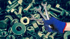 Hand holding the wrench on used nut and bolts for equipment industrial backgr Stock Photos