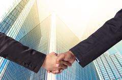 Hand shake between a businessman on Modern glass building background Stock Photos