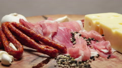 Close up of thin slices of prosciutto with dry raw sausages and swiss cheese - stock footage