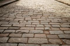 Perspective view of old paved road in town Stock Photos