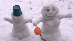 Two cheerful snowman with air orange ball in the street. Stock Footage