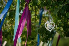 Summer tree in blue and violet blossom with wedding decoration - ribbons hearts Stock Photos