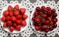 Plate with strawberries and a plate of red cherries on a lacy napkin, top vie Stock Photos