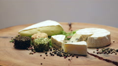 Varieties of cheese with herbs and peppercorns on a wooden board, rotating Stock Footage