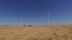 Eolic turbine wind renewable energy farm in wheat field steady shot 4k Stock Footage