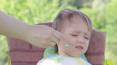 Mom tries to feed the baby with a spoon, but he refuses. - stock footage