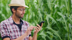 Attractive young farmer in hat speaks by mobile phone, smiling. Against a Stock Footage