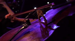 Concert, a woman musician hand playing the cello on stage, hand close up Stock Footage