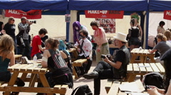 Zombie festival-people wearing zombie makeup and costumes sitting by the table Stock Footage