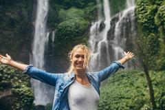 Tourist with tropical waterfall in background Stock Photos
