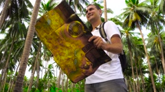 Young male traveler checking map in palm grove. Stock Footage