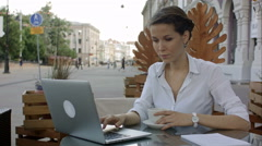 Woman using laptop and free wifi at outdoor cafe Stock Footage