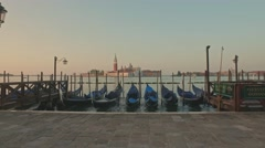 Parking gandolas on the Doge's palace embankment with the bell tower of the - stock footage