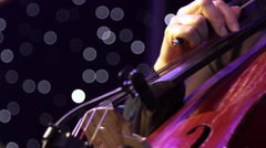 Concert, a musician pinching the strings cello, fingers close up Stock Footage