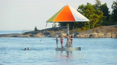 Time-lapse of kids playing on a water carousel, at a beach, in Hanko, Finland Stock Footage