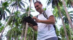 Young male traveler using tablet in palm grove. Stock Footage