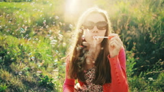 SLOW MOTION: Young woman in meadow blowing soap bubbles Stock Footage
