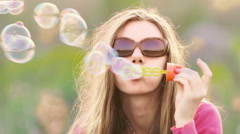 Young woman in meadow blowing soap bubbles - stock footage