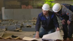 Engineers look at building plans and discuss stages of construction in heavy Stock Footage