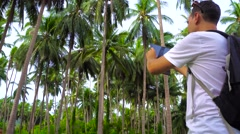 Young male traveler taking photo in palm grove. Stock Footage