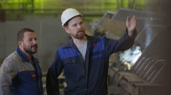 Two construction workers discuss stages of construction in heavy industry Stock Footage