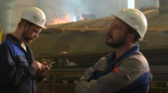 Portrait of two serious engineers at work in heavy industry factory. sparks and Stock Footage