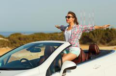 Beautiful woman sitting in cabriolet, enjoying trip on luxury modern car with Kuvituskuvat