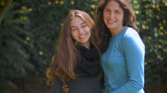 Two sisters hug, smile, and laugh for the camera in slow mo - stock footage