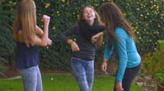 Teenage girls laughing and playing outside in slow motion Stock Footage