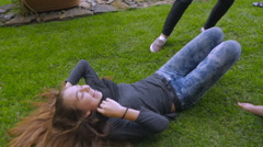 A teenage girl is lifted off the grass by her friends and then dances in slowmo Stock Footage