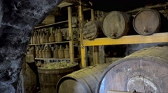Old wine cellar with oak barrels and glass bottles. Stock Footage