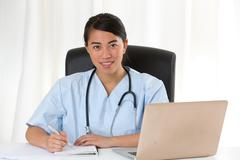 Reassuring Asian female doctor at desk looking at the camera Stock Photos