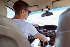 Young stylish man in sunglasses driving a car. View from the back, with the rear Stock Photos