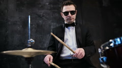 Man in black suit and sunglasses plays on drum. Rock cover band performing on Stock Footage
