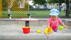 Little girl sitting in the sandbox and playing with molds on the playground - stock footage