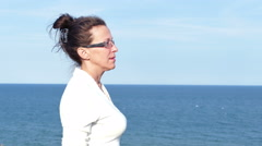 4K.Adult woman in spectacles and white blouse against sea surface Stock Footage