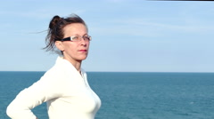 4K.Adult woman in spectacles and white blouse against sea surface - stock footage
