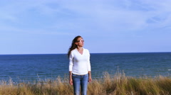 4K. Adult woman meditates against sea surface in windy day Stock Footage
